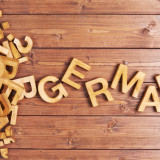 Word german made with block wooden letters next to a pile of other letters over the wooden board surface composition; Shutterstock ID 249255952; PO: license(21860)